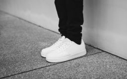 Photo of Person Wearing White Low-top Sneakers Standing Beside Wall Royalty Free Stock Image