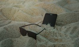 Photo of Phone and Sunglasses on Sand Stock Photos