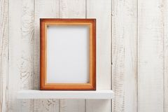 Photo picture frame at wooden shel. Photo picture frame at white wooden shelf Royalty Free Stock Image