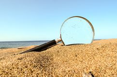 Magnify Glass on the Sand Beach. Photo Picture of a Loupe Magnify Glass on the Sand Beach Royalty Free Stock Images