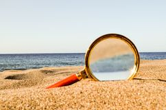 Magnify Glass on the Sand Beach. Photo Picture of a Loupe Magnify Glass on the Sand Beach Stock Images