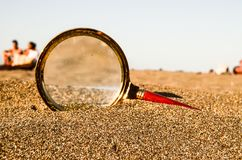 Magnify Glass on the Sand Beach. Photo Picture of a Loupe Magnify Glass on the Sand Beach Royalty Free Stock Photo