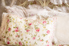 Photo of pillow with floral print on big bed Royalty Free Stock Images