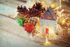 Photo of pine cones and decorative wooden house next to gold garland lights on wooden background. copy space. glitter overlay Royalty Free Stock Photos