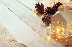 Photo of pine cones and decorative wooden house next to gold garland lights on wooden background. copy space. retro filtered.  Stock Image