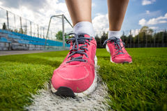 Photo of pink female sneakers on soccer grass field Royalty Free Stock Images