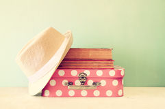 Photo of pink suitcase with polka dots, fedora hat and stack of books Royalty Free Stock Image