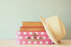 Photo of pink suitcase with polka dots, fedora hat and stack of books over wooden table, retro style image Stock Photos