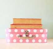 Photo of pink suitcase with polkadots and stack of books over wooden table, retro style image Royalty Free Stock Images