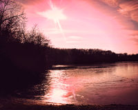 A photo of a pink sunset reflecting on ice of a lake. A pink sunset reflecting on thin ice on a lake with tree silhouettes Royalty Free Stock Images