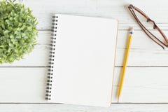 Photo plate de configuration de bureau sur le fond blanc, carnet vide Image stock
