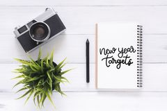 Photo plate de vue de configuration de bureau fonctionnant avec le carnet de calligraphie de cible de nouvelle année et d'un appa Images stock