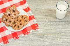 Photo of plate full of tasty cookies on checkered tablecloth and. Glass of milk on wooden table Stock Photos