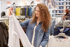 Photo of pleased female shopaholic chooses clothes for party, holds shirt on hangers, going to buy new outfit in shopping mall, sp royalty free stock photography