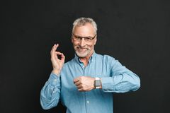 Photo of pleased gentleman 60s with grey hair wearing eyeglasses. Showing ok sign being on time isolated over black background Stock Image