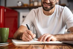 Photo of pleased man writing down notes while using silver laptop on kitchen table. Photo of pleased man 30s wearing eyeglasses writing down notes while using royalty free stock images