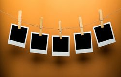 Five Blank Polaroid Frames Hanging on Twine. Photo polaroid colorful paper space business empty Royalty Free Stock Photos