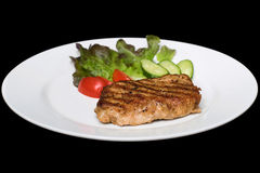 Photo of a pork stake on a white plate with a cucumber, tomato a Stock Photography