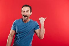 Photo of positive bearded man 30s in casual blue t-shirt advertising product with pointing finger backward on copyspace, isolated. Photo of positive bearded man stock images