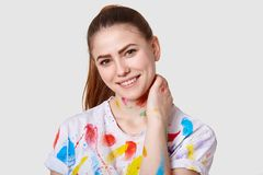 Photo of positive European woman keeps hand on neck, smiles broadly, has colourful watercolour stains, has dark hair with pony stock images