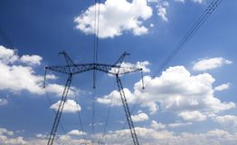 Photo of power transmission tower. High voltage pillar on blue sky background stock photography