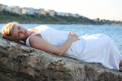 Photo of pregnant woman lying touching her tummy near ocean Royalty Free Stock Photos