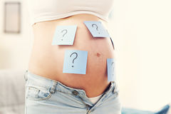 Photo of pregnant woman with question marks on belly royalty free stock photo