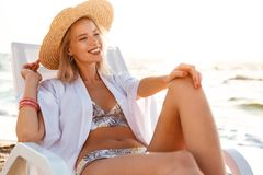 Photo of pretty blonde woman 20s in swimsuit and straw hat smili. Ng while lying in deck chair at sea coast during summer sunrise Royalty Free Stock Images