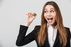 Photo of pretty businesswoman looking at golden bitcoin isolated. Photo of pretty brunette businesswoman in suit looking at golden bitcoin in hands isolated Royalty Free Stock Photos