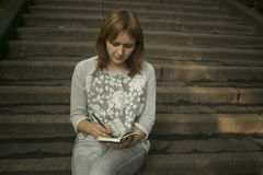 Photo of pretty girl sitting on stairs of college. And writing something Stock Images
