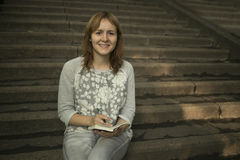 Photo of pretty girl sitting on stairs of college. And writing something Stock Photos
