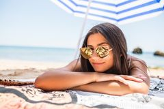 Pretty woman in sunglasses in swimsuit lying on sandy beach with colorful beach umbrella near sea. Photo of pretty girl in swimsuit lying on sandy beach with royalty free stock images