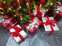 Many Christmas presents under the tree. Photo of pretty red and silver christmas presents under a tree royalty free stock photos