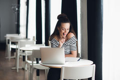 Photo of pretty woman fiddling with pen and thinking over a subject while sitting in some coffee shop with her laptop. Photo of pretty woman fiddling with pen Royalty Free Stock Image