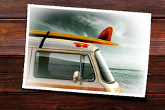 Photo Print. Wooden table with old photographic print of a van with a surfboard Royalty Free Stock Images