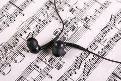 Music sheet with headphones. Photo of printed Music sheet and headphones Royalty Free Stock Photos