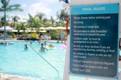 Pool Rules Signage. A photo of a private resort pool blurred in the background showing pool rules and maximum occupancy royalty free stock image