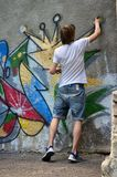 Photo in the process of drawing a graffiti pattern on an old concrete wall. Young long-haired blond guy draws an abstract drawing of different colors. Street royalty free stock photos