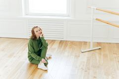 Photo of professional female dancer has rest after training, poses on floor near ballet barre, has ballet classes, wears green royalty free stock image