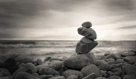 Photo of the pyramid of the stones on ocean background. Sepia style. stock images