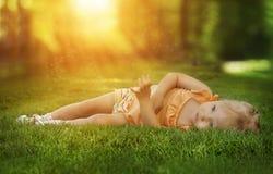 Photo rêveuse d'une petite fille dans l'herbe Image stock