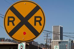 Rail Road Tracks Crossing Sign. This is a photo of a rail road crossing sign in front of a cityscape Royalty Free Stock Photography