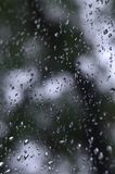 A photo of rain drops on the window glass with a blurred view of the blossoming green trees. Abstract image showing cloudy and ra. Iny weather conditions Stock Image