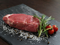 Raw steak. Photo of a raw thick sirloin steak with rosemary, cherry tomatoes, salt and peppercorns on a piece of black slate Royalty Free Stock Photography
