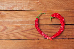 Photo of red heart shape chili pepper on wooden background Stock Image