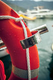 Photo of red lifebuoy with rope against sea port. Closeup photo of red lifebuoy with rope against sea port Royalty Free Stock Images
