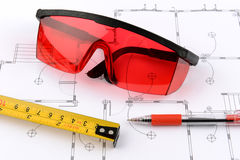 Photo red protective spectacles and red pen and measuring tape Stock Images