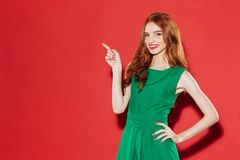 Redhead young happy lady in green dress pointing. Royalty Free Stock Photo