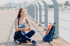 Photo of relaxed cheerful fitness girl in sporswear, sits crossd legs outdoor, rests after long walk, listens music with cellular. And headphones, rucksack near royalty free stock images