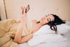 Beautiful young smiling brunette woman using phone in her bedroom. Photo of relaxed woman with black hair watches online story on cell phone, reads post with stock image